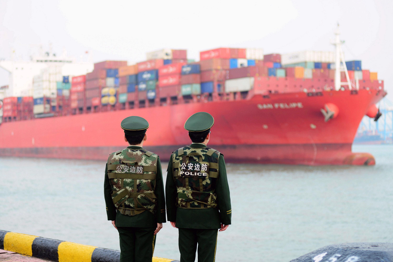 Membros das forças de segurança da fronteira ficam na frente de um navio de carga do porto de Qingdao em Shandong