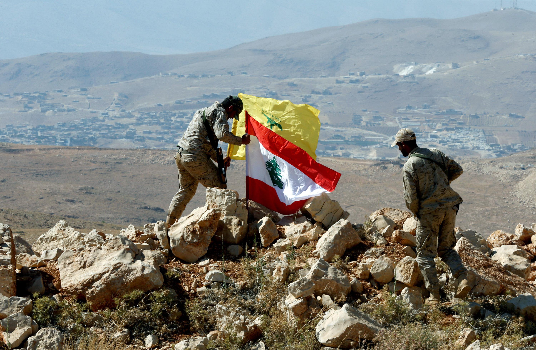 Hezbollah fighters put Lebanese and Hezbollah flags at Juroud Arsal, Syria-Lebanon border