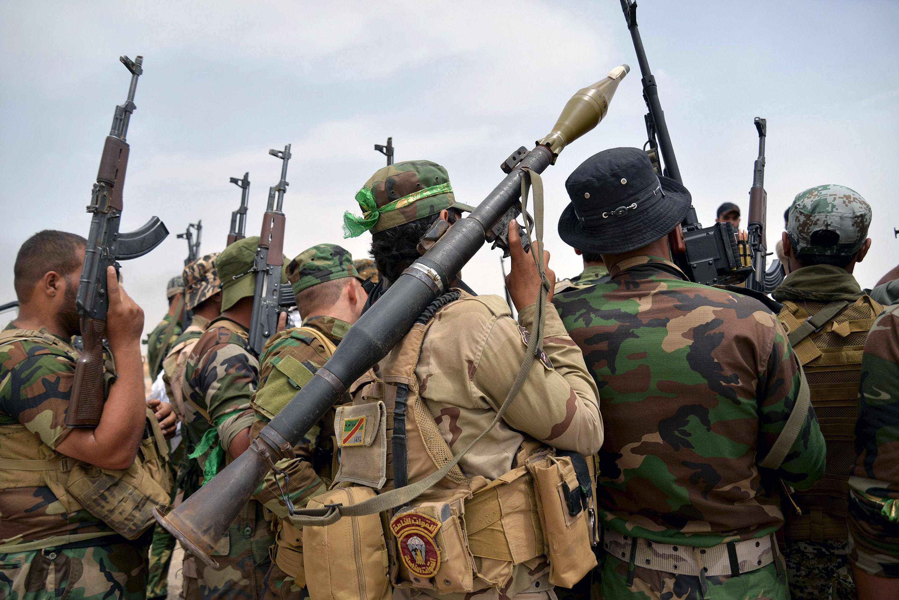 Iraqi Shiite paramilitary personnel carry their weapons as they gather on the outskirt of Bayji
