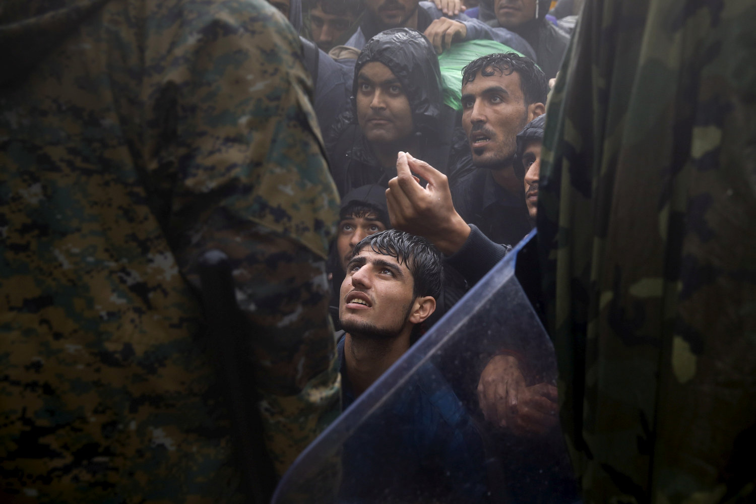 Migrants and refugees beg Macedonian policemen to allow passage to cross the border from Greece into Macedonia during a rainstorm, near the Greek village of Idomeni, September 10, 2015. REUTERS/Yannis Behrakis/File Photo