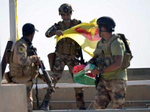 Member of Iraqi security forces holds Kurdish flag in Kirkuk