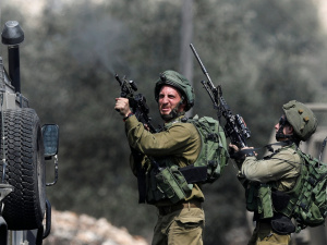 An Israeli soldier fires a weapon during clashes with Palestinian protesters following a protest against the near-by Jewish settlement of Qadomem, in the West Bank village of Kofr Qadom near Nablus August 25, 2017. REUTERS/Mohamad Torokman