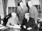 Photograph of President Truman in the Oval Office with British Prime Minister Clement Attlee, during Attlee's visit to the United States to discuss the Korean crisis, as Secretary of State Dean Acheson and Secretary of Defense George C. Marshall look on.