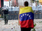 A man with a Venezuelan flag stands in front of riot security forces while rallying against Venezuela's President Nicolas Maduro's government in Caracas