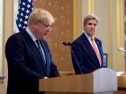 """Image: """"U.S. Secretary of State John Kerry listens to newly installed British Foreign Secretary Boris Johnson addresses reporters in the gilded Lacarno Media Room in the Foreign & Commonwealth Office in London U.K., on July 19, 2016, during a news conference following their first bilateral meeting. [State Department Photo/ Public Domain]"""""""