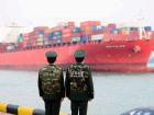 Members of border security forces stand in front of a docking cargo ship at Qingdao port in Shandong