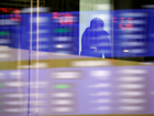 A visitor is seen as market prices are reflected in a glass window at the TSE in Tokyo