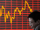 A investor reacts in front of an electronic board showing stock information at a brokerage house in Taiyuan, Shanxi province October 12, 2009. China's key stock index closed 0.59 percent lower on Monday, led by Sinopec Corp, as huge supplies of new shares, including listed stocks freed up after the expiry of lock-up periods, offset the positive impact of market-friendly government steps. REUTERS/Stringer