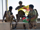 Member of Iraqi security forces holds Kurdish flag in Kirkuk