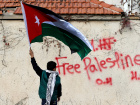 A boy holds the Jordanian national flag during a protest near the U.S. Embassy in Amman