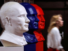 "A woman walks past busts depicting Russian president Vladimir Putin in the colours of the Russian national flag at the ""SUPERPUTIN"" exhibition in UMAM museum in Moscow"