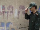 A member of Iran's Revolutionary Guard walks past anti-U.S. graffiti as he arrives to attend a ceremony to mark the death anniversary of the Islamic Republic founder Ayatollah Ruhollah Khomeini at a mosque in northern Tehran June 2, 2008. REUTERS/Morteza Nikoubazl (IRAN)