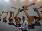 A man walks past a billboard at 2017 China International Robot Show in Shanghai, China July 5, 2017. REUTERS/Aly Song