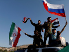 Syrians wave Iranian, Russian and Syrian flags during a protest against U.S.-led air strikes in Damascus,Syria April 14,2018.REUTERS