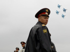 Policemen stand guard as Russian Air Force Sokoly Rossii (Falcons of Russia) aerobatic team on their SU-27 jet fighters perform during a demonstration flight at the Moscow International Air Show (MAKS) in Zhukovsky, Moscow region, 23 August 2009. REUTERS/Denis Sinyakov