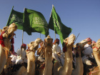 Saudis riding camels wave the country's national flag during celebrations of the 7th anniversary of Saudi King Abdullah's accession to the throne, in Ashwaq city near Tabouk, 1500 km (932 miles) from Riyadh May 21, 2012. Picture taken May 21, 2012. REUTERS/Mohamed Alhwaity