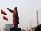 A statue of former Chinese leader Mao Zedong is seen in front of smoking chimneys at Wuhan Iron And Steel Corp in Wuhan, Hubei province, March 6, 2013. China will impose new restrictions on its sprawling steel sector as it battles chronic air pollution, but hopes that the curbs could also help tackle sector overcapacity and strengthen the country's struggling state-owned mills are likely to be dashed. Picture taken March 6, 2013. REUTERS/Stringer