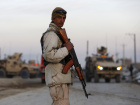 A member of the Afghan security personnel stands guard at the site of a suicide car bomb attack in Kabul
