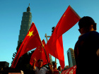 Pro-China supporters hold Chinese national flags in front of landmark building Taipei 101, outside the dinner venue of Sha Hailin, a member of Shanghai's Communist Party standing committee, in Taipei, Taiwan.