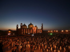People greet one another after evening prayers led by Sheikh Saleh bin Ibrahim Imam Qaba at the Badshahi Mosque in Lahore, Pakistan