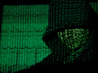 A projection of cyber code on a hooded man