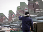 A serviceman carries a air-to-ground missile next to Sukhoi Su-25 jet fighters during a drill