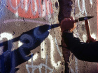 A man from West Berlin uses a hammer and chisel to chip off a piece of the Berlin Wall in 1989. Wikimedia Commons/Public domain