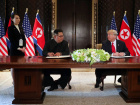 U.S. President Donald Trump and North Korea's leader Kim Jong Un look at each others before signing documents that acknowledge the progress of the talks and pledge to keep momentum going, after their summit at the Capella Hotel on Sentosa island in Singapore June 12, 2018. They are flanked by Kim Yo Jong, sister of North Korean leader Kim Jong Un, and U.S. Secretary of State Mike Pompeo. REUTERS/Jonathan Ernst