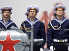 Russian sailors stand at attention on board a vessel during their departure to return to Russia at a port in Qingdao, Shandong province