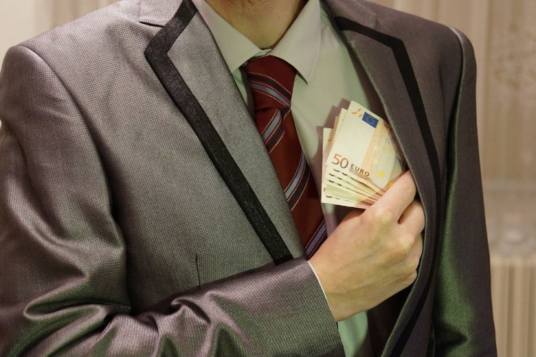 Image: A man in a suit putting money in his pocket. Public domain photo by Kiwiev.