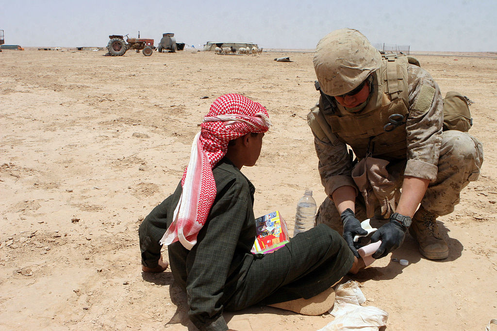 A U.S. Navy Corpsman gives medical care to an Iraqi child in the Al Anbar province. Wikimedia Commons/U.S. Marine Corps