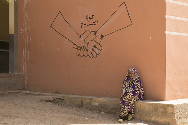 """Image: """"A Moroccan woman rests by a sign reading 'the power of reconciliation,' May 18, 2015, in Larbaa Salhel, Morocco, during humanitarian/civic assistance operations as part of Exercise African Lion 15. U.S., Tunisian and Moroccan military medical and dental personnel are providing services to local Moroccans throughout the exercise to build partnerships between nations and with the local people. (U.S. Marine Corps photo by Cpl. Elizabeth A. Case)"""""""