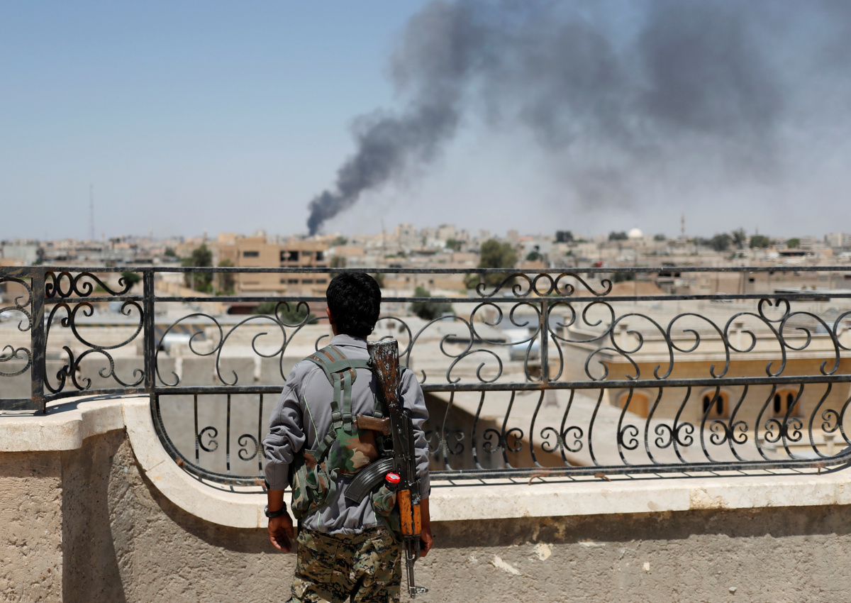 A Kurdish fighter from the People's Protection Units (YPG) looks at a smoke after an coalition air strike in Raqqa.