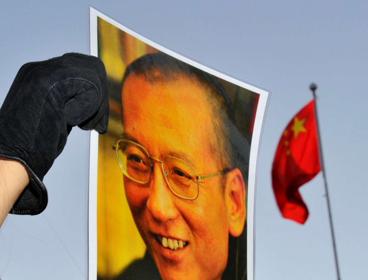 A protester holds an image of jailed dissident Liu Xiaobo outside the Chinese Embassy in Oslo, Norway December 9, 2010. REUTERS/Toby Melville/File Photo