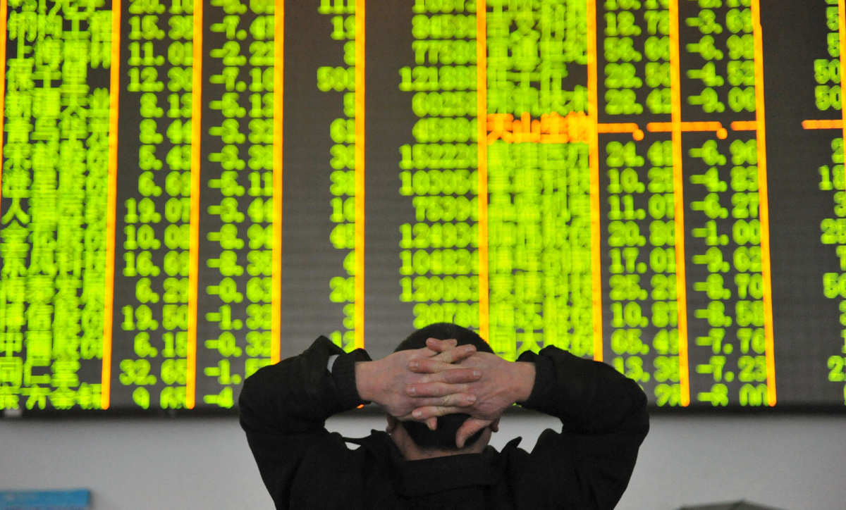 An investor looks at an electronic screen at a brokerage house in Hangzhou