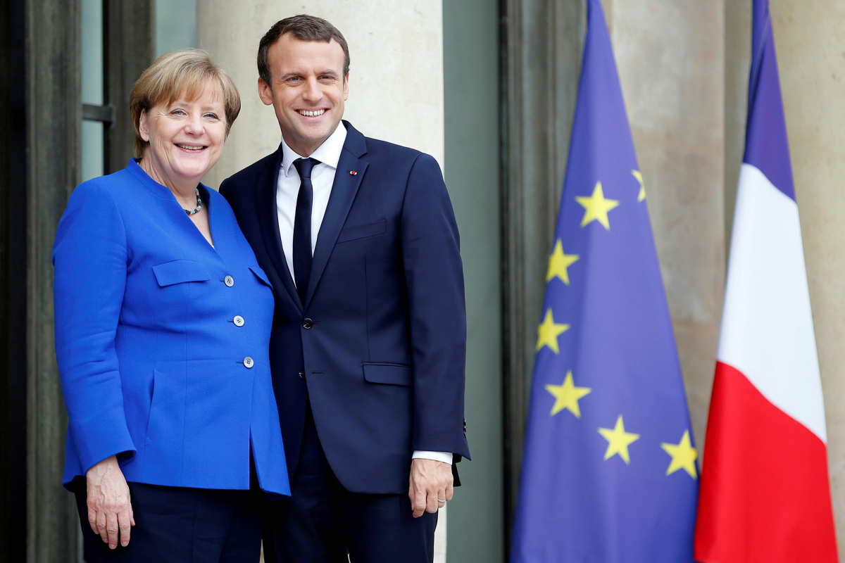 French President Emmanuel Macron arrives with German Chancellor Angela Merkel to attend a Franco-German joint cabinet meeting at the Elysee Palace in Paris, France, July 13, 2017. REUTERS/Stephane Mahe.