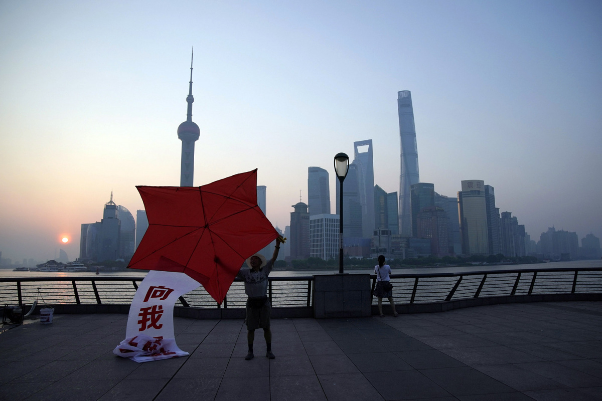 A man poses with a kite shaped like the red star of China's People's Liberation Army on the bund in front of the financial district of Pudong in Shanghai