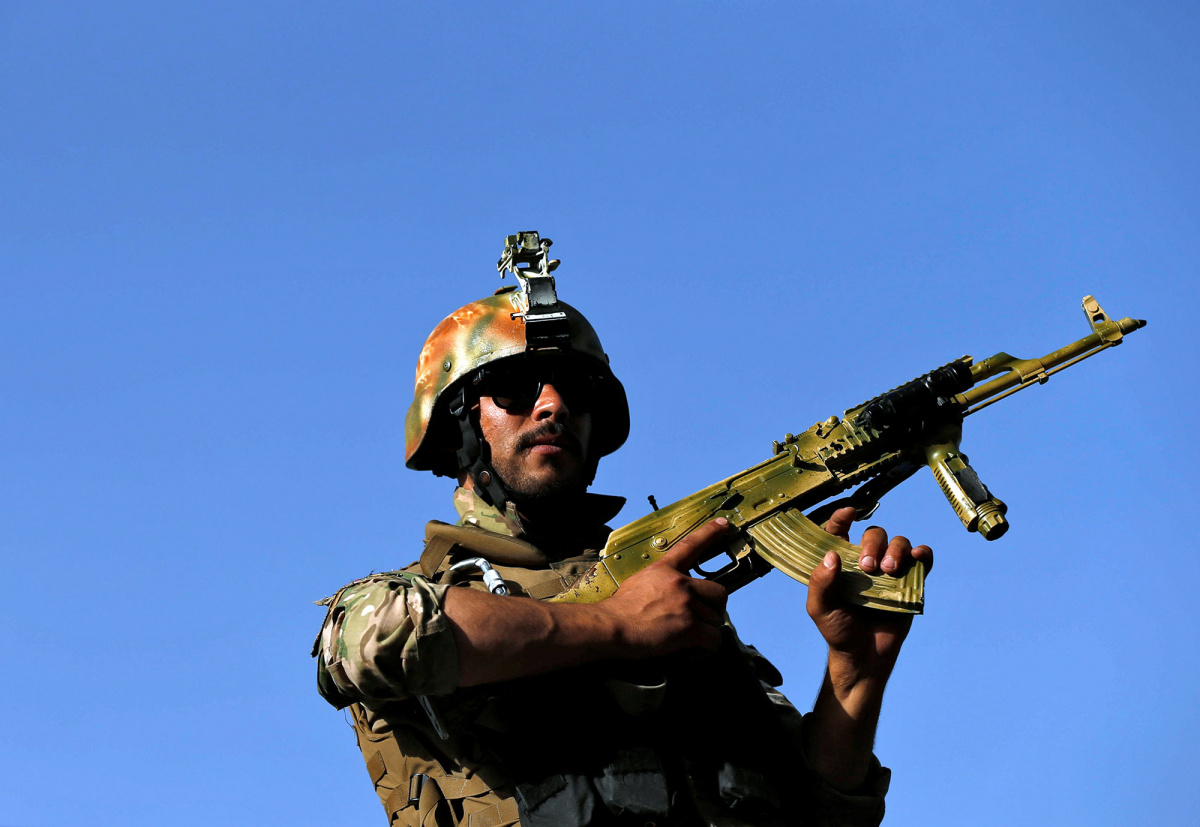 An Afghan security forces member leaves the site of an attack on the Iraqi embassy after a battle in Kabul
