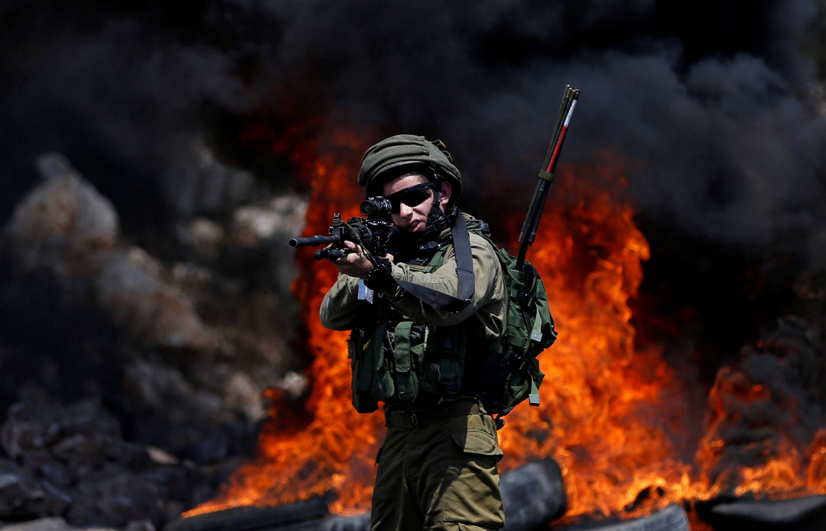 An Israeli soldier walks points his weapon toward Palestinian protesters during clashes in the West Bank village of Kofr Qadom near Nablus August 11, 2017. REUTERS/Mohamad Torokman