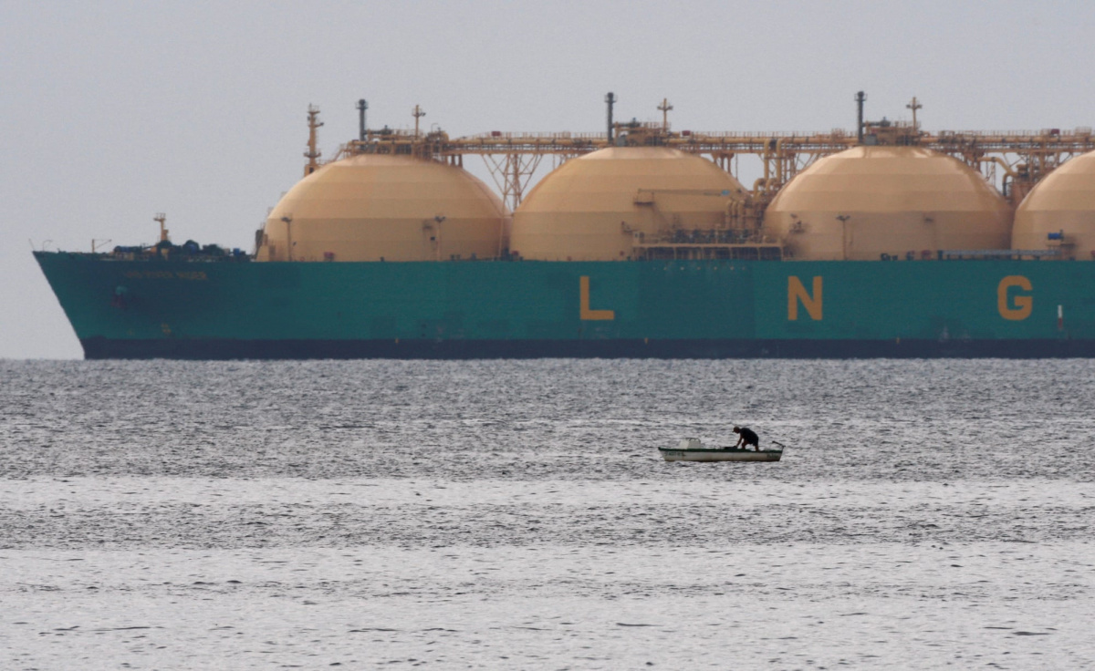A fisherman stands in a boat as a liquid natural gas tanker passes the coast near Havana