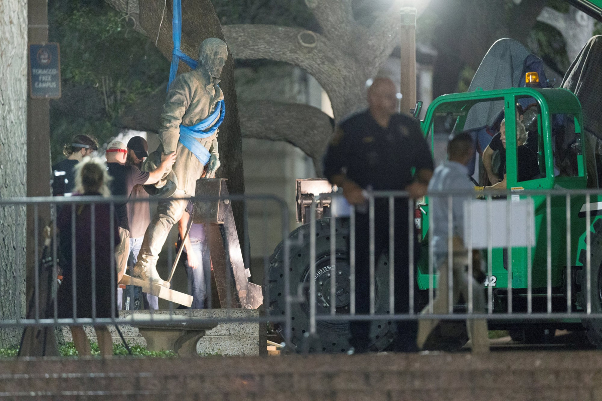 Workers remove a statue of Robert E. Lee from the south mall of the University of Texas in Austin
