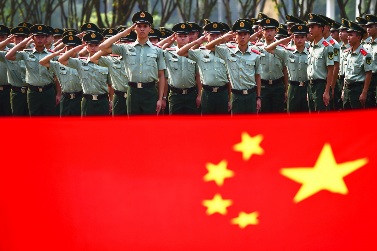 Retiring paramilitary policemen take their oaths in front of a Chinese national flag during their farewell ceremony in Shenzhen