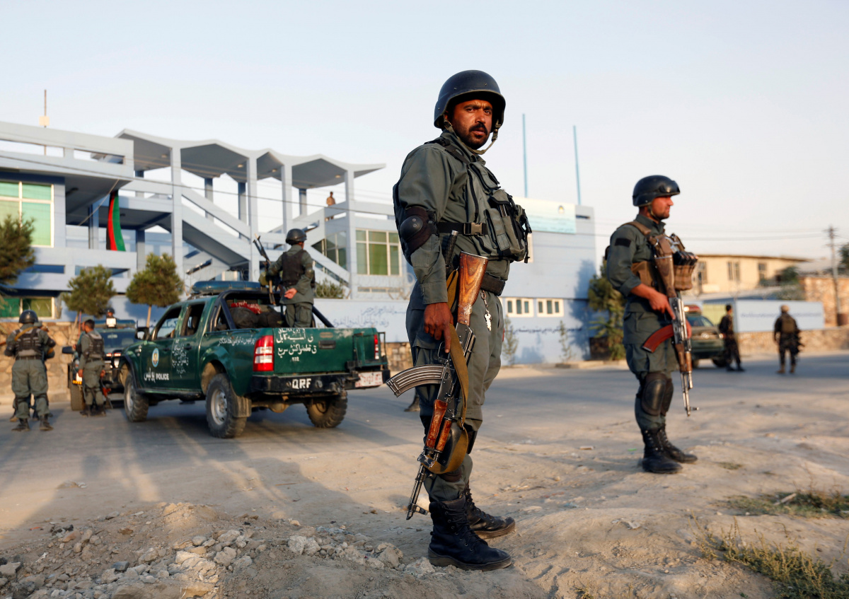 Afghan police officers stand guard at the site of a suicide attack in Kabul, Afghanistan