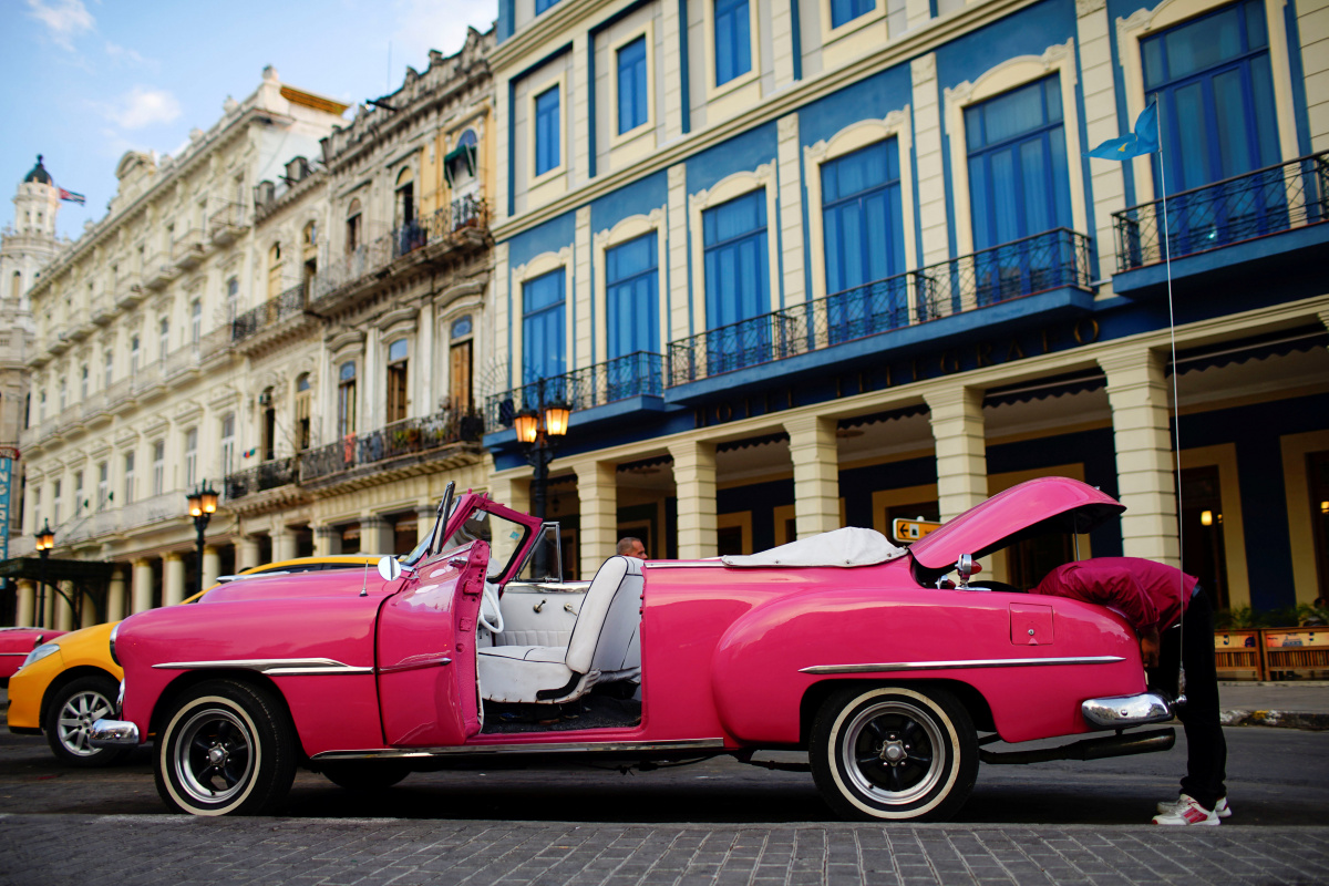 A vintage car driver checks his back lights as he waits for tourists in Havana, Cuba
