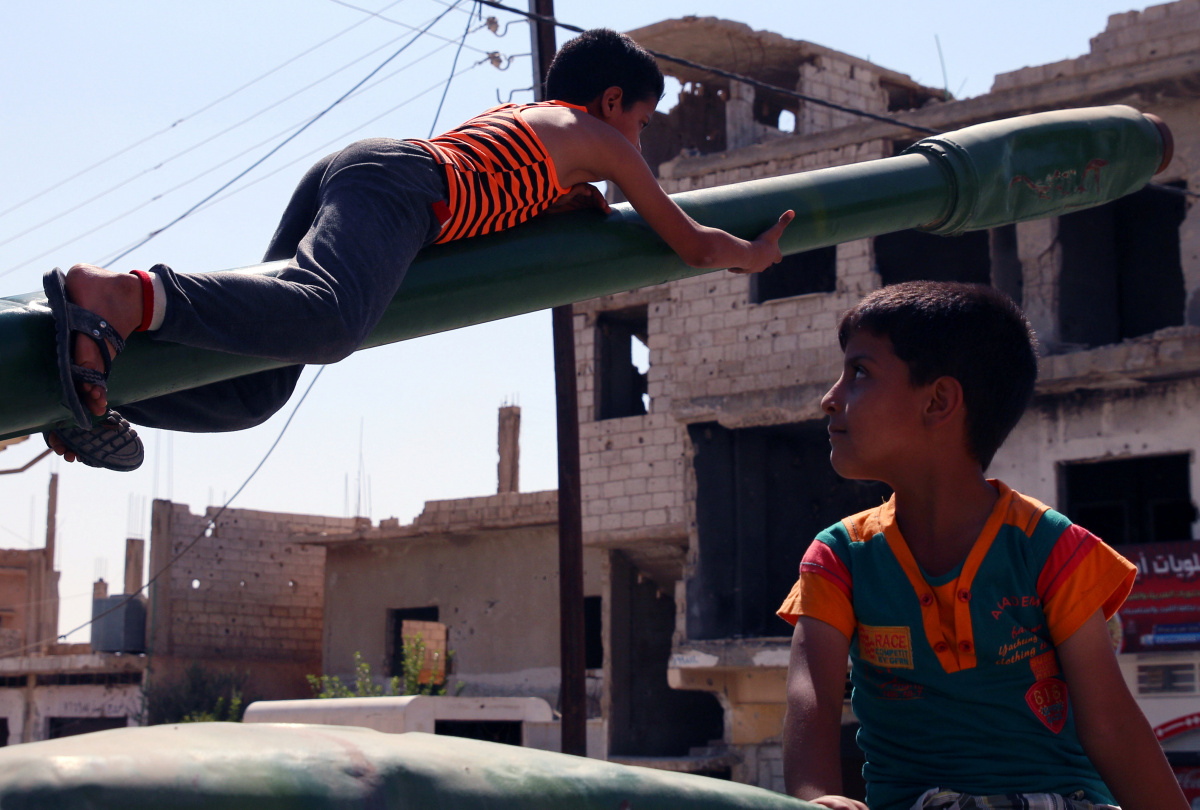 Boys play on a damaged military tank that belonged to forces loyal to Syria's President Bashar al-Assad in the rebel-held southern town of Bosra al-Sh