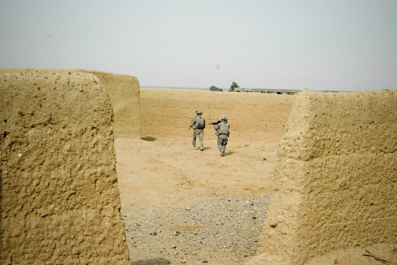 """Capt. Matthew Quiggle, commander of Alpha Troop, 8th Squadron, 1st Cavalry Regiment, 5th Stryker Brigade Combat Team, leads a search of a structure in a village after discovering a young Afghan boy digging a hole nearby."" DVIDS, Public Domain."