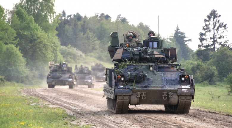 """Image: """"M2A3 Bradley Fighting Vehicles road march back to their tactical assemble area after a situational training exercise lane as a part of Combined Resolve VI at Hohenfels, Germany May 16. Combined Resolve VI is a squadron-level decisive action rotation at the Joint Multinational Readiness Center May 5-25 that is training 5th Squadron, 7th Cavalry Regiment on cavalry and reconnaissance tasks. (Photo courtesy of Ralph Zwilling)"""""""