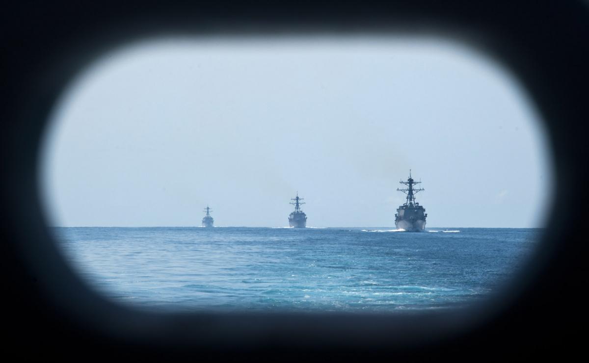 The Arleigh Burke-class guided missile destroyers USS Kidd (DDG 100), USS Pinckney (DDG 93), and USS Dewey (DDG 105) steam the South China sea behind the Nimitz-class aircraft carrier USS John C. Stennis (CVN 74)