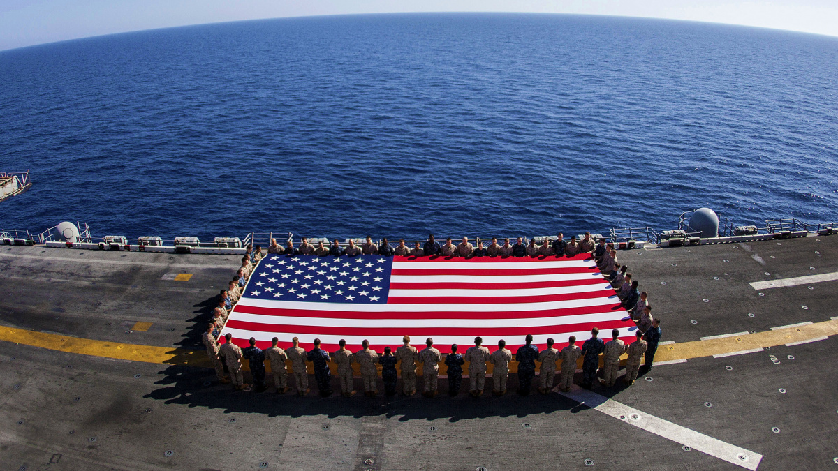 U.S. Marines and Sailors assigned to the 26th Marine Expeditionary Unit (MEU), and Sailors assigned to the USS Kearsarge (LHD 3), hold the American flag to commemorate the Fourth of July during their 2013 deployment on the flight deck of the USS Kearsarge, at sea, July 4, 2013. DoD photo by Sgt. Christopher Q. Stone, U.S. Marine Corps/Released. U.S. Department of Defense Flickr