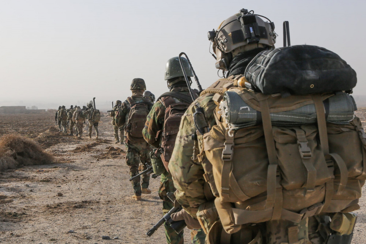 A U.S. Army Special Forces Soldier with Combined Joint Special Operations Task Force-Afghanistan and Afghan National Army commandos with the 3rd Company, 3rd Special Operations Kandak move toward a compound during a clearance operation in Bahlozi, Maiwand district, Kandahar province, Afghanistan